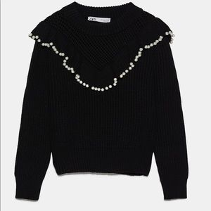 Ruffled sweater with pearls.